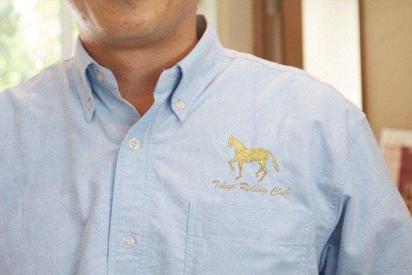 オックスシャツには高級感あふれるゴールドのロゴマーク