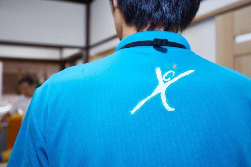 ドライポロシャツの後ろ襟下に、元気に運動する人をイメージしたイラストを大きめにプリント