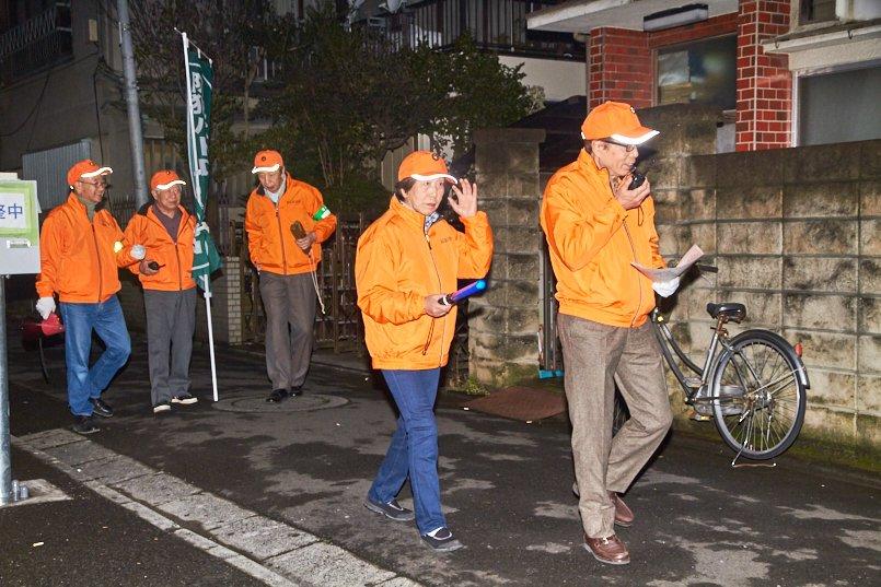 プリントを入れたオレンジの軽防寒ブルゾンと蛍光オレンジのキャップを着用
