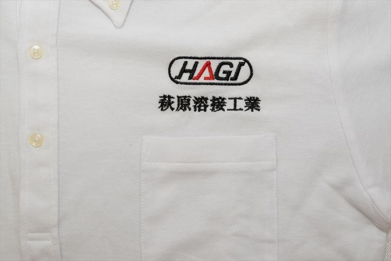 左胸に赤と黒の糸を使い、「HAGI」をアレンジしたロゴマークと社名を刺繍
