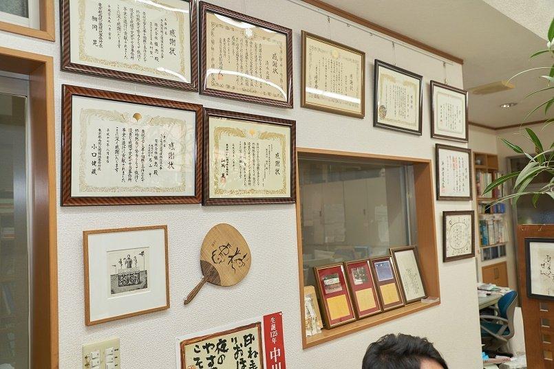 たくさんの賞状と記念品が飾られたオフィス