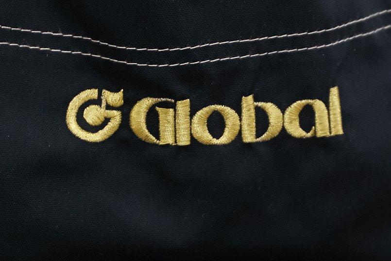 エプロンの正面に「G」の文字と八分音符をかたどったロゴマークを刺繍